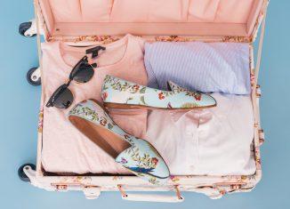 Valise remplie pour les vacances avec des t-shirts, des lunettes de soleil et des chaussures fleuries