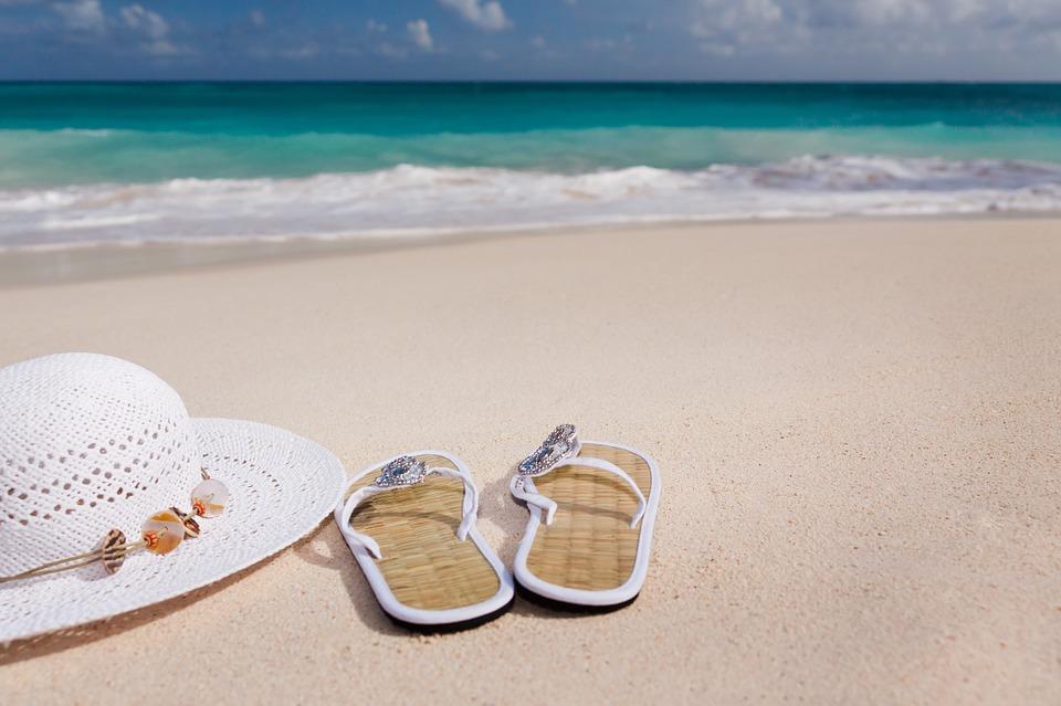 Paire de tongs et chapeau de paille posés sur la plage en bord de mer